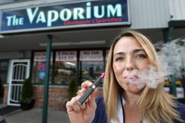 "In this Tuesday May 3, 2011 picture, Kim Thompson exhales vapor from her e-cigarette outside her new business called ""The Vaporium"" in Lakewood, Wash. Thompson, a 20-year smoker, opened the business selling electronic cigarettes or personal vaporizers as an alternative to traditional cigarettes in January and says the business is doing well. The Tacoma-Pierce County Health Department is considering a ban on battery-powered electronic cigarettes that deliver nicotine without smoking. The News Tribune reports that regulations proposed Wednesday, May 4, 2011 would ban e-smoking _ or ""vaping"" _ in the same public places where the use of real cigarettes and cigars are prohibited by state law. King County adopted such a ban in January.  (AP Photo/The News Tribune, Dean J. Koepfler)"